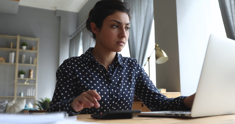 Serious young indian woman calculate domestic bills pay loan payment online on laptop sit at home office desk, focused businesswoman using computer calculator plan expenses manage finances concept Royalty-Free Stock Footage #1037437013