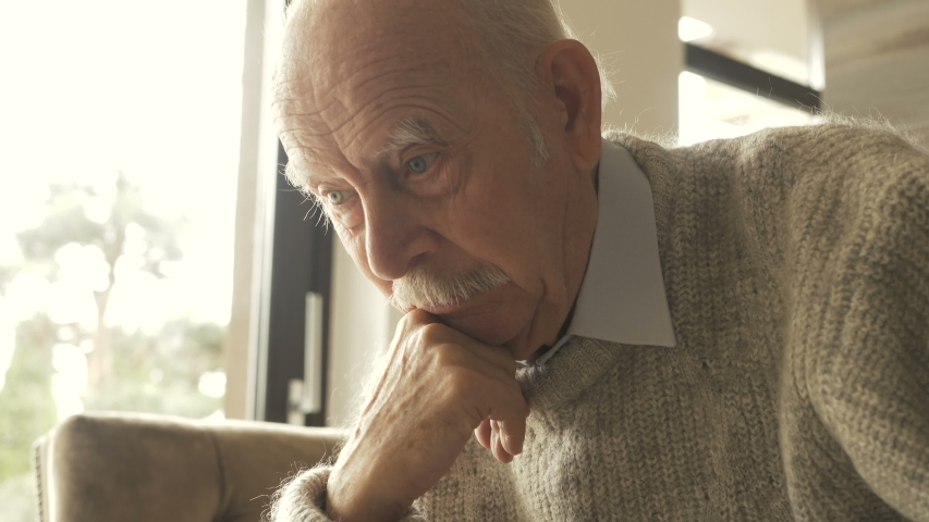 Pensive elder senior man looking away feel upset, thoughtful melancholic older retired gray haired grandpa suffer from sorrow grief loneliness, sad grandfather widower alone at home, close up view | Shutterstock HD Video #1037442689