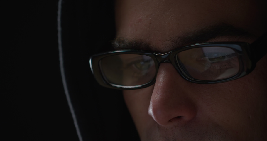 Head shot close up of a young Caucasian man wearing a black hoodie and glasses sitting, looking down and typing on a computer, the reflection of the screen visible in his glasses  #1037445431