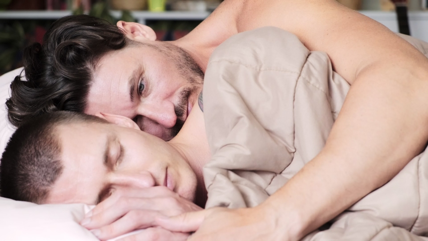Young gay male couple in bed together, intimate. Hugging each other. Happy gay friendship, relationship, pride concept. | Shutterstock HD Video #1037465021