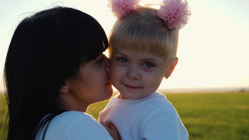 A happy family. Young mother hugs little daughter in a field in the sun at sunset. Tenderness of family relationships. Concept of family love. | Shutterstock HD Video #1037468507