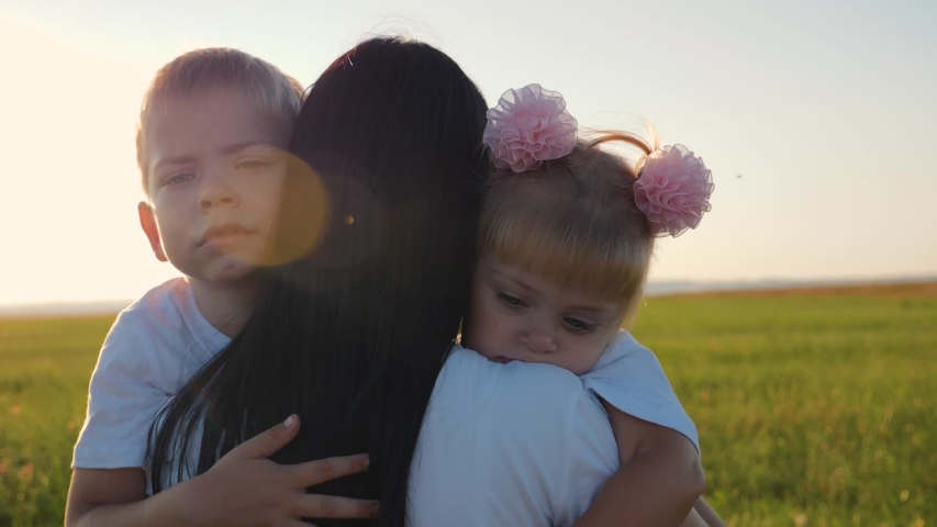 A happy family. A young mother hugs her two young children, laughing in a field in the sun at sunset. Family love concept | Shutterstock HD Video #1037468585