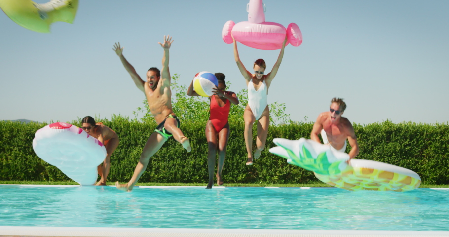 Slow motion of young multi-ethnic friends in swimwear are having fun to enjoy their summer vacation together in swimming pool with colorful inflatables in a sunny day.