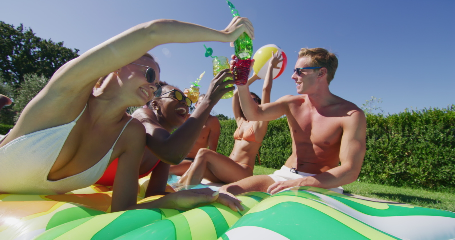 Authentic shot of young multi-ethnic friends in swimwear are relaxing on colorful inflatables and cheering with cocktails in swimming pool for celebrate a start of their vacation together.   Shutterstock HD Video #1037471441