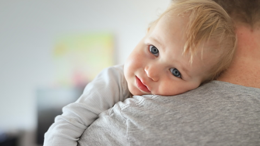 Close-up portrait of cute adorable blond caucasian toddler boy on fathers shoulder indoors. Sweet little child smiling feeling safety on daddys hand. Responsibility and childcare. happy childhood   Shutterstock HD Video #1037483231