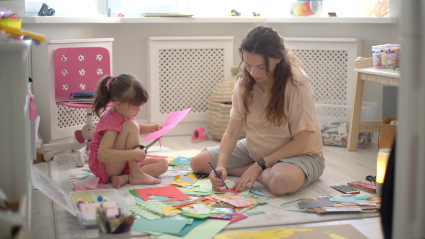 Young happy pregnant mother and young daughter sit on the floor in the children's room and doing arts and crafts, drawing together. Pregnant mother preparing an older child for a new baby. Royalty-Free Stock Footage #1037484941