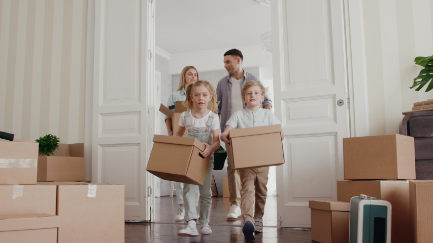 Happy Family Moves in New Home. Positive Looking at Relocating by Mom and Adult Dad with Furniture Packing in Modern Room. Casual Relax Child Emotion and Unpack by Small Son and Beautiful Daughter
