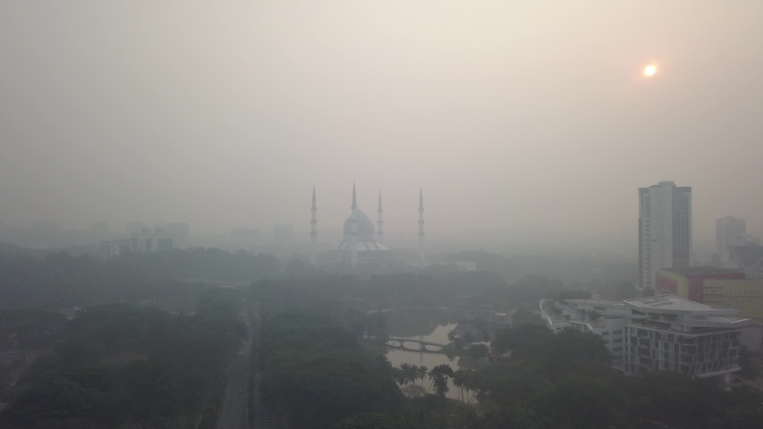 Malaysia, September 2019 - Aerial video of Sultan Salahuddin Abdul Aziz Shah Mosque during a hazy sunrise. The haze is back in Malaysia due to open forest burning in Indonesia. Noise in clip. | Shutterstock HD Video #1037500721