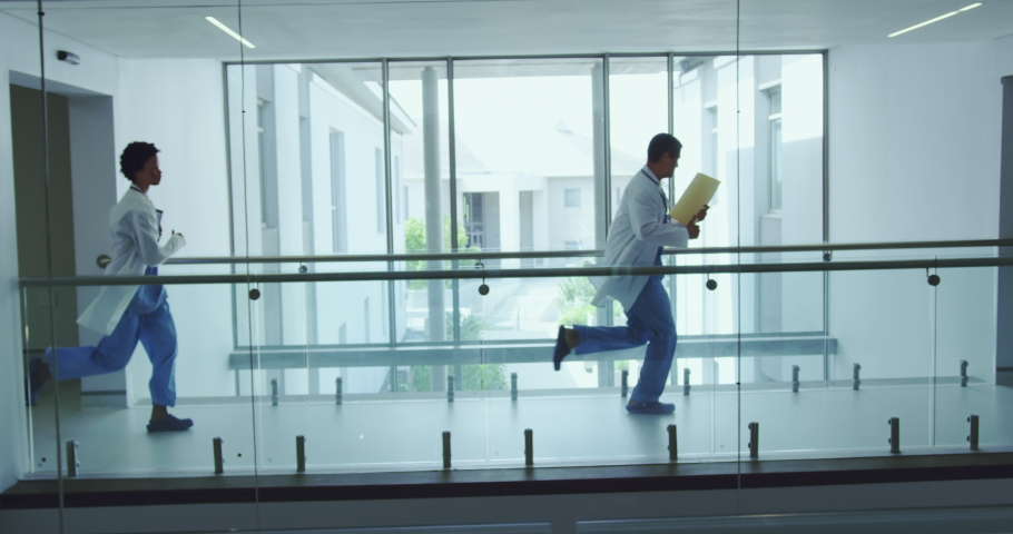Side view of diverse male and female doctors running in the corridor at hospital. They are holding medical files. Healthcare workers in the Coronavirus Covid19 pandemic  Royalty-Free Stock Footage #1037502806