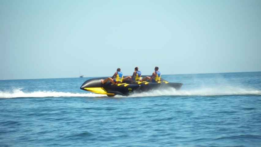 group of people ride water rides on sea. on large air mattress. Batman