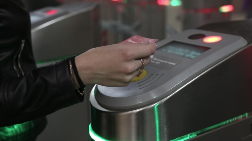 Red and green light on subway turnstile. persons apply electronic touch card, people pass through opened doors. metro metal wicket control panel, paying for entrance
