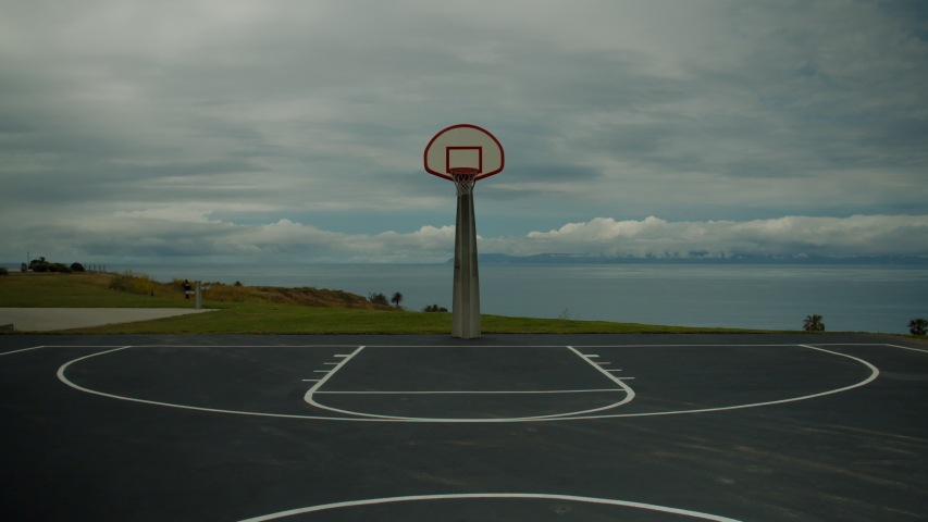 View of an empty scenic basketball court on a ocean shore. No people