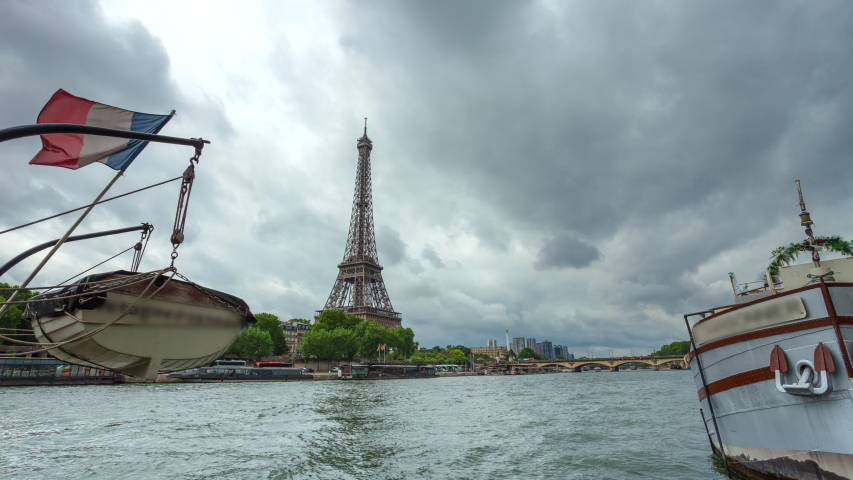Eiffel Tower and river boats on the zooming time lapse with cloudy sky in Paris, France. Summer cityscape, city life, vacation and touristic places in Europe.