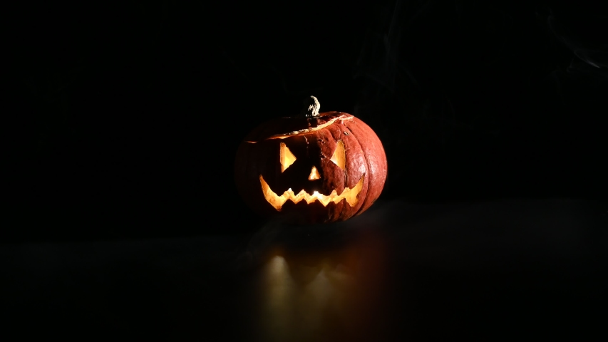 Halloween, orange pumpkin with a scary luminous face on a dark background. Thick gray smoke comes out and spreads across the black table. A close-up of a flashlight on the eve of all the saints   Shutterstock HD Video #1037537957