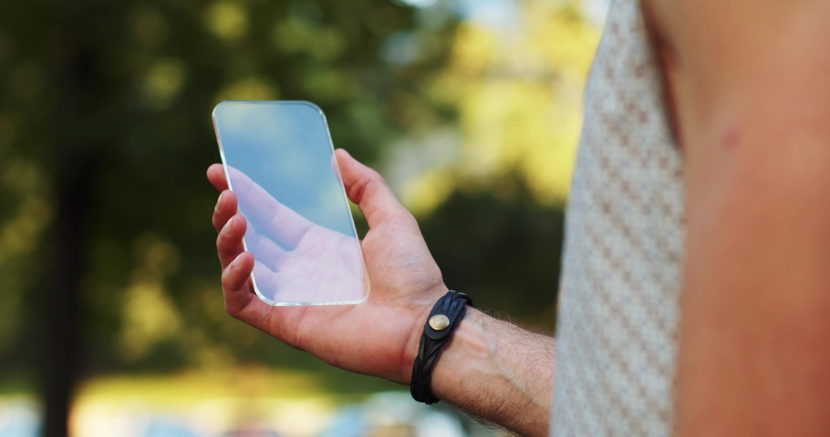 Close-up young man holding mock-up transparent smartphone virtual display modern technology on green park background. | Shutterstock HD Video #1037543984