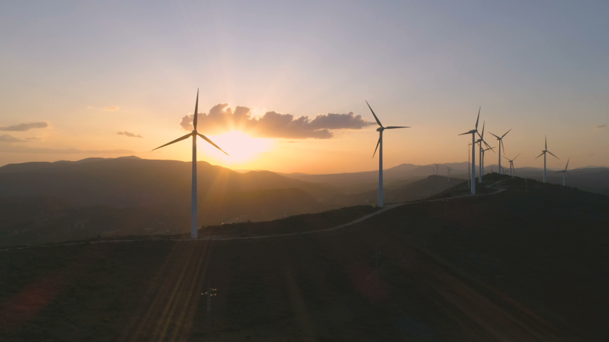 Wind turbine farm on beautiful golden hour evening mountain landscape. Renewable energy production for green ecological world. Aerial view of wind mills farm park on evening mountain. Flying forward