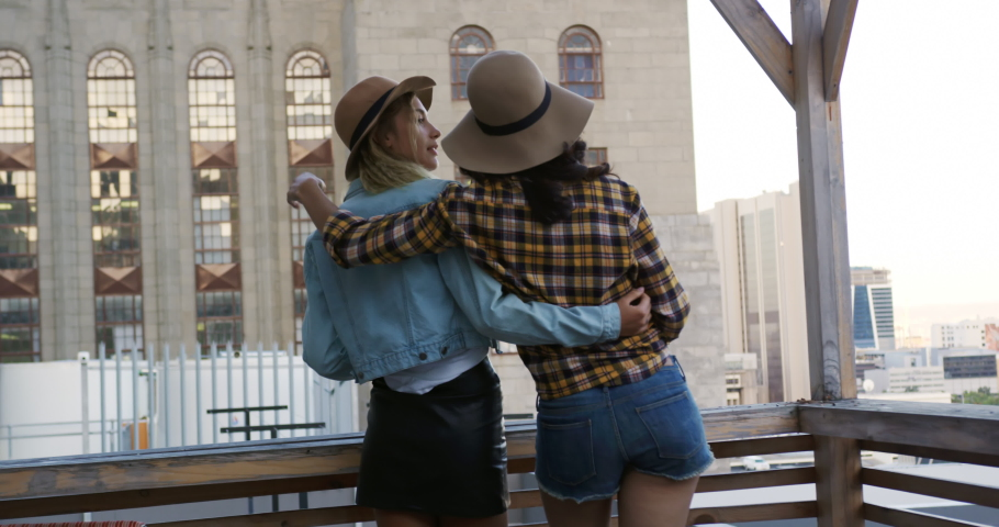 Rear view of a happy young Caucasian and mixed race female friends enjoying themselves at a party on a rooftop, embracing and admiring the view, with a building in the background | Shutterstock HD Video #1037549585