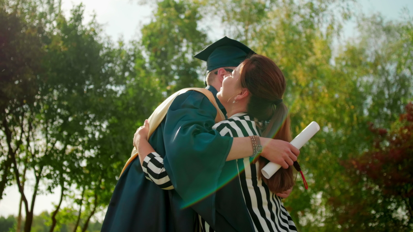 Excited Graduate Student in Gown and Cap with Diploma Hugs his Friend after Graduation Ceremony. 4K Slow Motion Medium Close-Up Shot with Beautiful Sun Lens Flare