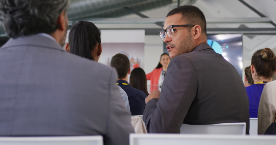 Side view close up of a young Caucasian businessman wearing glasses sitting in the audience at a business conference presentation, turning around and talking over his shoulder  | Shutterstock HD Video #1037564366
