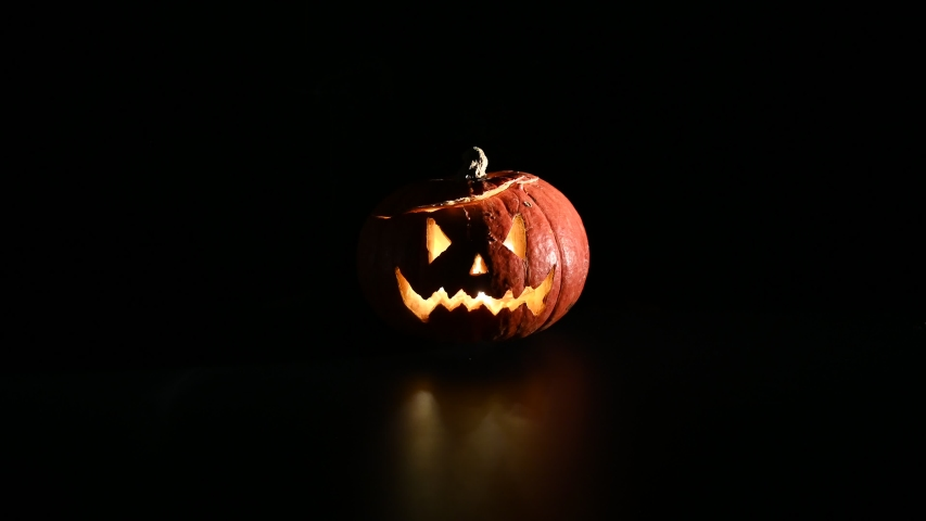 Halloween, orange pumpkin with a scary luminous face on a dark background. Thick gray smoke comes out and spreads across the black table. A close-up of a flashlight on the eve of all the saints   Shutterstock HD Video #1037569502