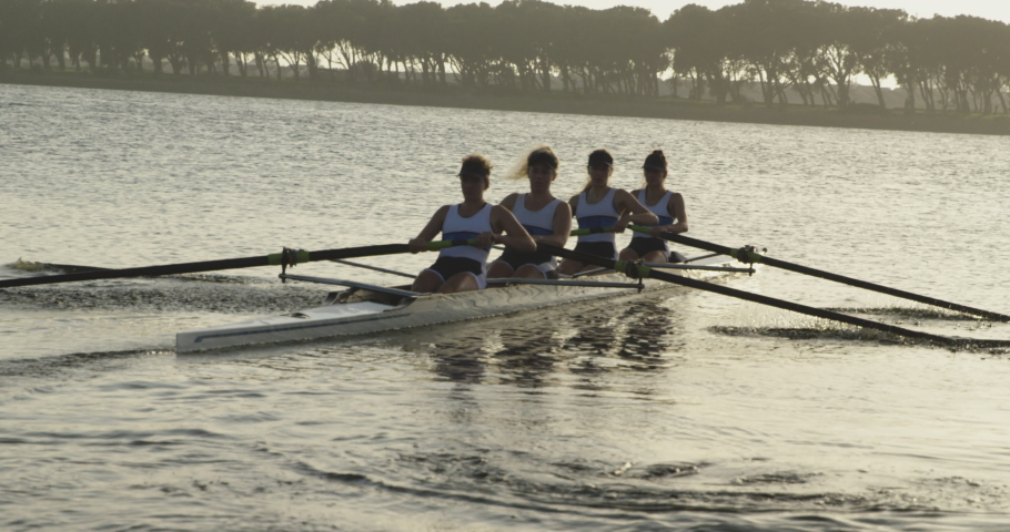 Front view of a team of four young adult Caucasian women rowing in a racing shell training on a river in slow motion