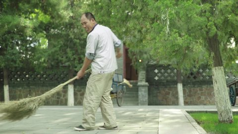 BEIJING, CHINA - SEPTEMBER 3, 2016. Male janitor with broom. Beijing. China. Asia