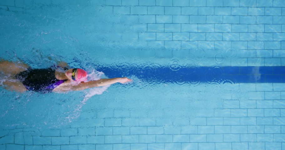Overhead view of a young female swimmer training in a swimming pool, backstroke