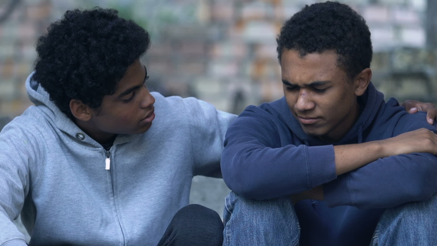Afro-American teen boy with bruised face hugging brother sitting alone on stairs