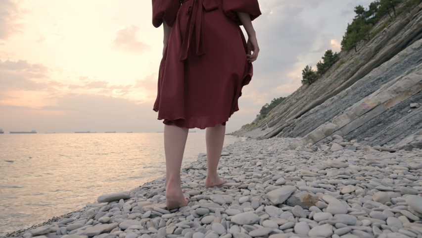 Close-up of the legs of a young girl with a red dress from behind walking on a rocky beach the sea coast at sunset. A dress fluttering in the wind in the wind.   Shutterstock HD Video #1037596310