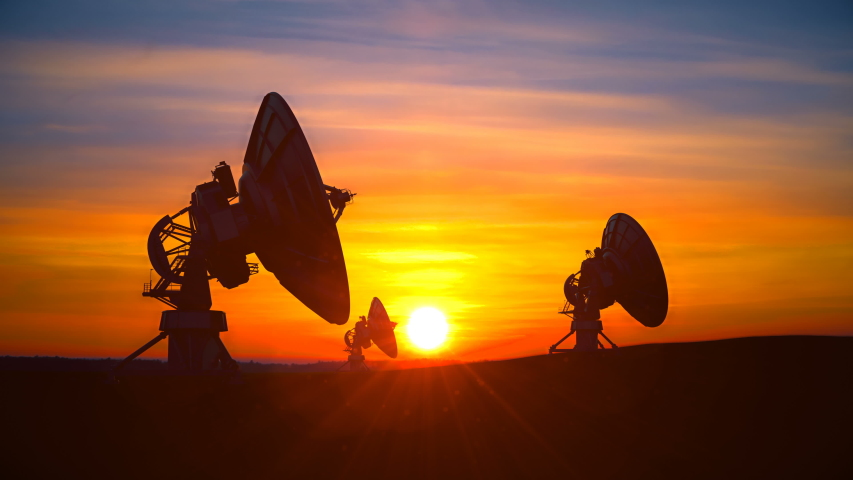 Three large radio telescope antennas against scenic sunset sky raise its dishes up exploring evening sky. Radio telescopes are used in science for space observation and distant objects exploring. Royalty-Free Stock Footage #1037597798