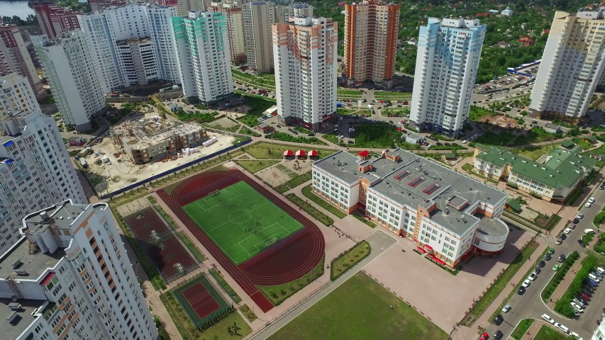 Residential high rise building and school with sports ground in schoolyard. Aerial view modern architecture apartment buildings. Residential area infrastructure | Shutterstock HD Video #1037603186