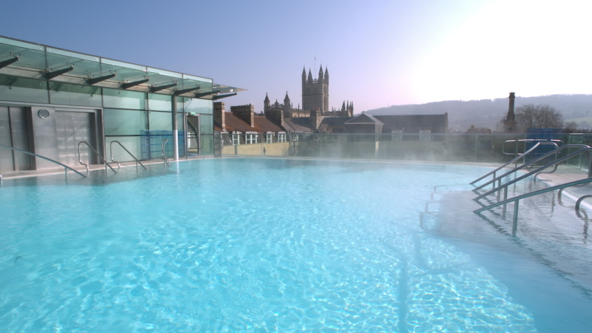 Steamy rooftop thermal pool in historic Roman city of Bath Spa in England with Bath Abbey cityscape in the background | Shutterstock HD Video #1037604806