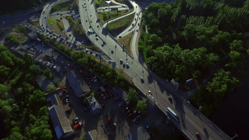 Cars driving on road junction in modern city at summer day. Aerial view car traffic on highway intersection. Modern crossroad in developed city   Shutterstock HD Video #1037607122