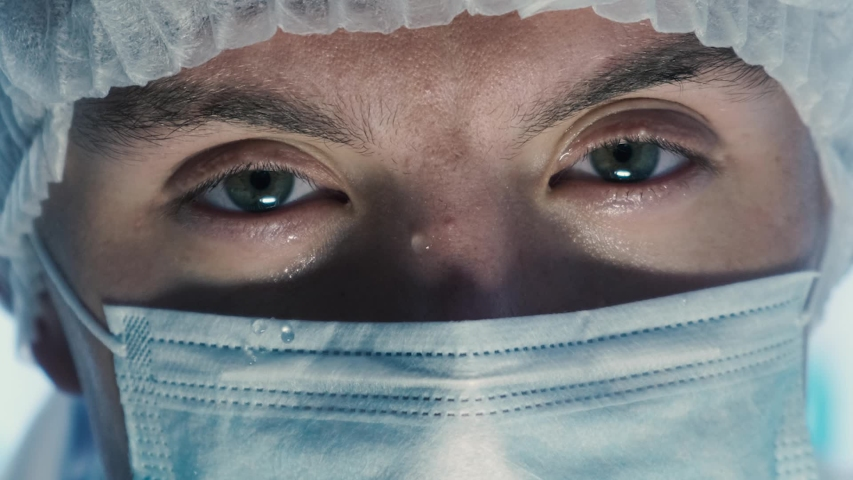 Upset masked doctor looking at the camera and lowering his eyes, close up. Failed operation Royalty-Free Stock Footage #1037617907