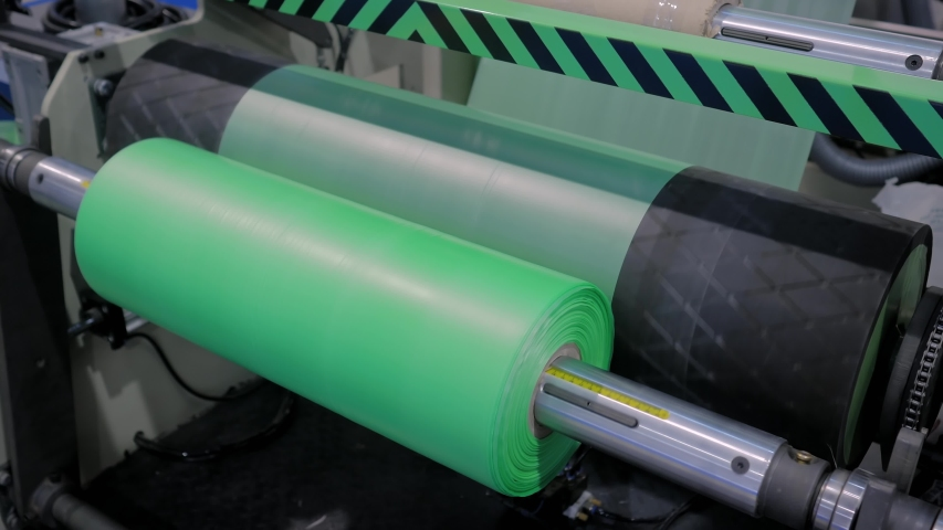 Manufacturing, recycling, industry and automated technology equipment concept. Part of automatic plastic bag making machine - moving roller with flat polyethylene green film at exhibition, trade show | Shutterstock HD Video #1037618327