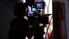 Movie Making Back View of Cameraman Shooting Film. Professional Filmmaker Woman Working with Camera at Dark Studio. Television Scene Production. Female Operator. Footage Shot Full HD 1080p