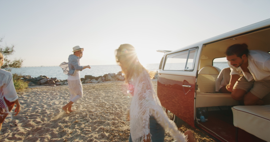 Slow motion of group of young multi-ethnic friends just arrived with a minivan are happy to start their vacation  and having fun on a beach with a sea on a sunset. | Shutterstock HD Video #1037631422