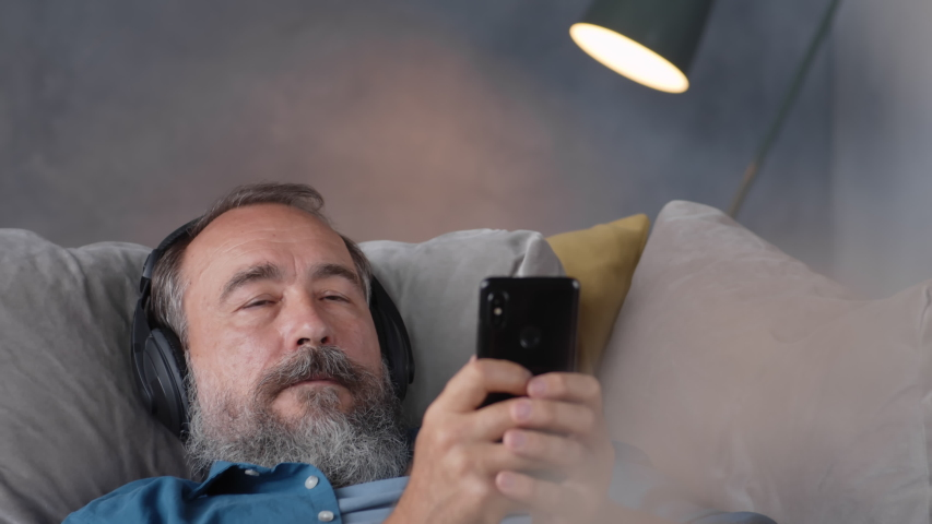 Close up of elderly man with headphones on his head lying on couch and turning audio book on his mobile phone then looking at camera