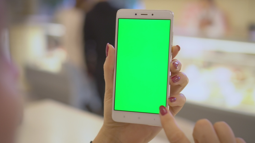 Business woman using smartphone viewing green screen on mobile phone browsing chroma key online watching enjoying drinking coffee in cafe reading social media close up hands | Shutterstock HD Video #1037646497