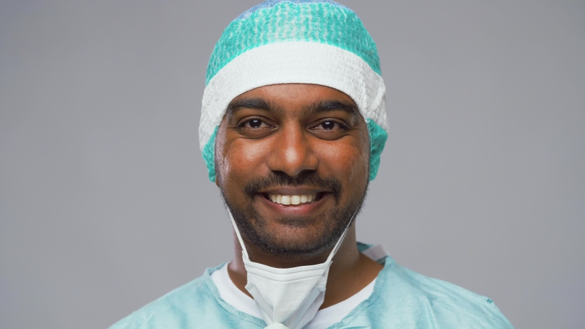 Medicine, science and surgery concept - indian male doctor, surgeon or scientist taking off safety glasses and protective mask over grey background | Shutterstock HD Video #1037657564