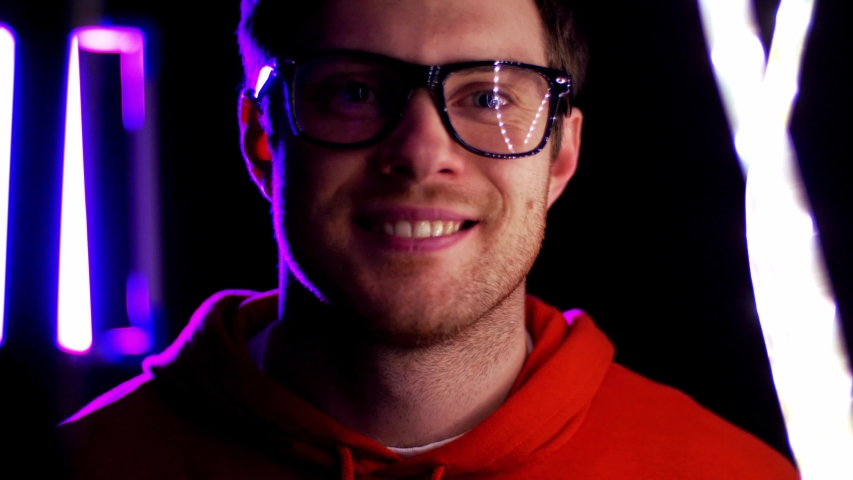 Vision, eyewear and people concept - portrait of smiling young man in glasses over ultra violet neon lights in dark room with glowing lines visual effect