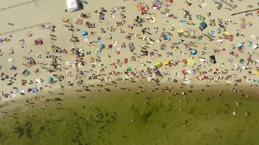 Aerial view of the beach in Gdansk, Poland.  The beach is located on the shores of the Baltic Sea. Crowds of people swim and sunbathe on the Baltic Sea on a hot sunny day. Drone Shot 4K. | Shutterstock HD Video #1037658104