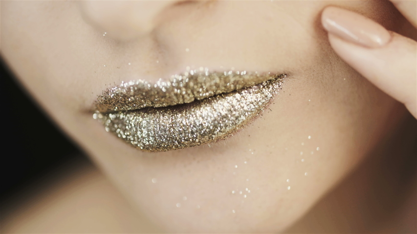 Gold lipstick. Golden makeup. Close up of beautiful lips of a girl with golden sparkles. Fingers and lips of a girl close-up. Clean skin.  Jewelry Advertising. | Shutterstock HD Video #1037660732