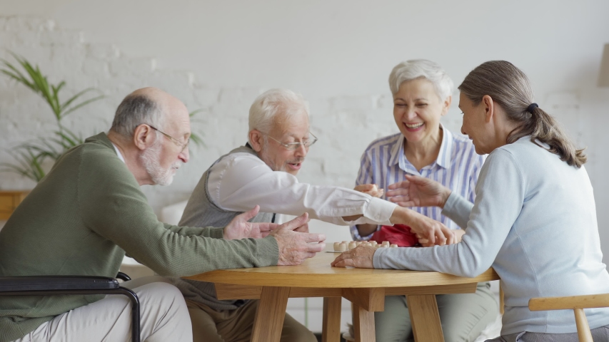 Tracking shot of group of four cheerful retired senior people, two men and two women, having fun sitting at table and playing bingo game together in nursing home #1037667410