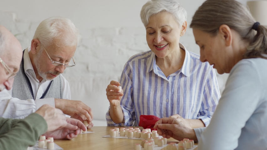 Tracking medium shot of group of four cheerful elderly people, two men and two women, having fun sitting at table and playing bingo game together in nursing home Royalty-Free Stock Footage #1037667836