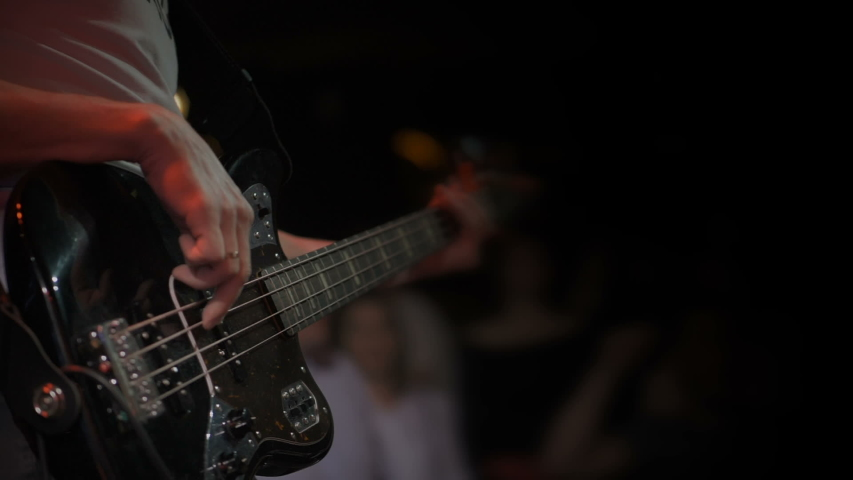 Guitarist performs on stage. Musician plays in slow motion. Closeup guitar view. Metal concert. Rock gig. Guitar strings. Rock music band. Music player. Electric guitar. Young music artist. Slowmo  | Shutterstock HD Video #1037667983