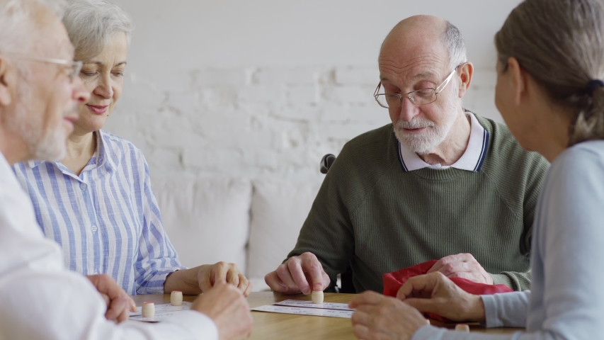 Group of four joyful elderly people, two men and two women, having fun sitting at table together and playing bingo game in nursing home, tracking medium shot Royalty-Free Stock Footage #1037670389