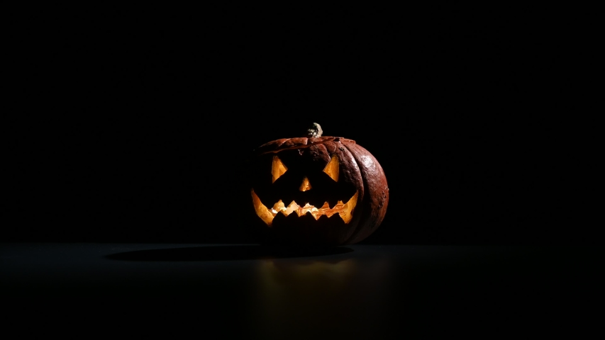 Halloween, orange pumpkin with a scary luminous face on a dark background. Thick gray smoke comes out and spreads across the black table. A close-up of a flashlight on the eve of all the saints | Shutterstock HD Video #1037674046