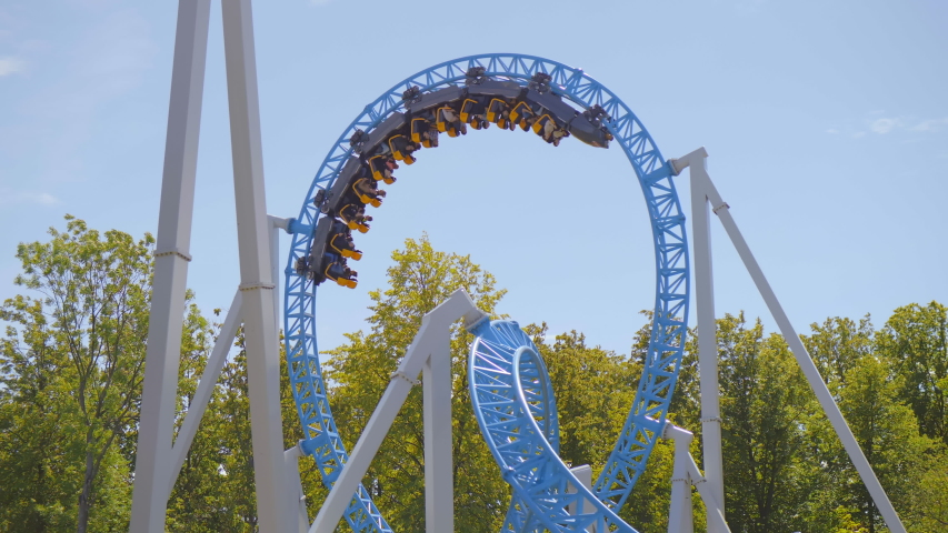 People in multiple cars ride on roller coaster in amusement park. Weekend activities