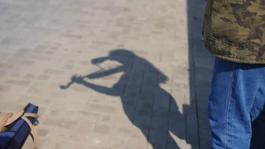 Shadow on the pavement of young girl plays the violin on the promenade for tourists in the summer. Close up shot.   Shutterstock HD Video #1037681231